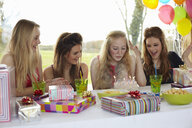 Teenage girl blowing out birthday candles with friends - CUF33782