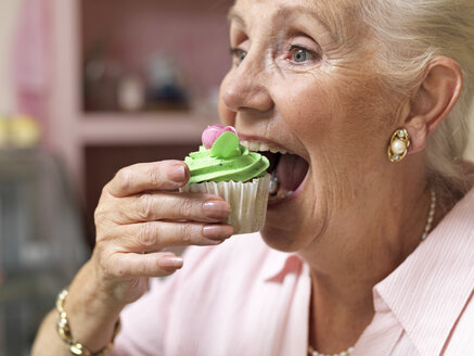Senior woman enjoying cupcake in cafe - CUF33812