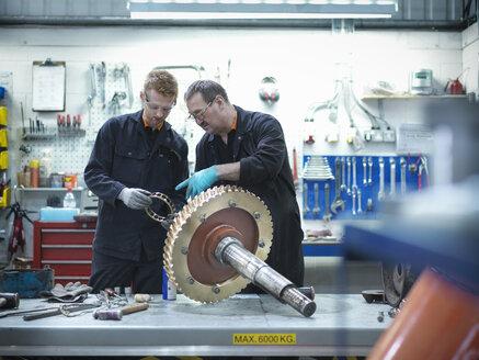 Engineer teaching apprentice in engineering factory - CUF33842
