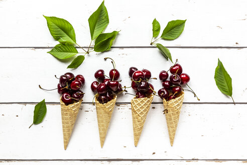 Row of four ice cream cones and  cherries on white wood - SARF03794