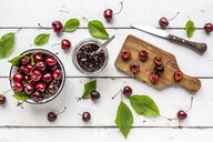 Jar of cherry jam and cherries on white wood - SARF03800