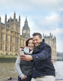 Mature tourist couple photographing selves and Houses of Parliament, London, UK - CUF33936