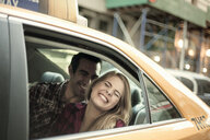 Young couple laughing in yellow cab, New York City, USA - CUF33960