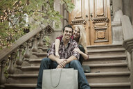 Young couple sitting on traditional city apartment steps - CUF33972
