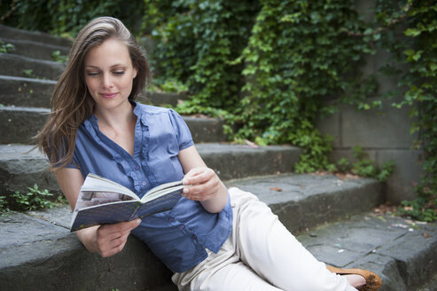 Woman sitting on step looking at book - CUF33987