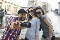 Tourist friends taking self portrait, Plaza de la Virgen, Valencia, Spain - CUF34002