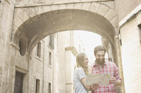Young couple looking at map outside Valencia Cathedral, Valencia, Spain - CUF34011