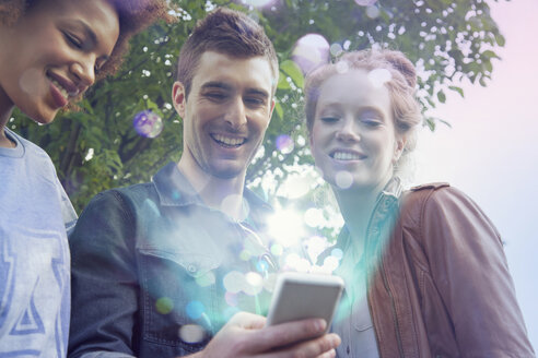 Three friends looking at smartphone with lights coming out of it - CUF34026
