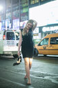 Young woman carrying high heels on night out, New York City, USA - CUF34044
