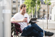 Man with rolling suitcase and takeaway coffee sitting on bench using tablet - UUF14274