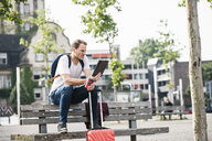 Man with rolling suitcase and takeaway coffee sitting on bench using tablet - UUF14280