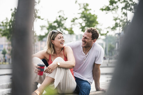 Happy couple sitting on a bench - UUF14289
