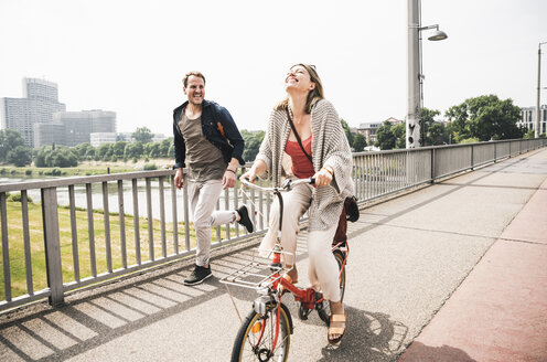 Happy couple crossing a bridge with bicycle and by foot - UUF14304