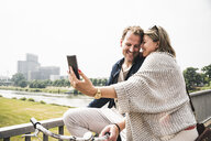 Happy couple taking a selfie on a bridge - UUF14307