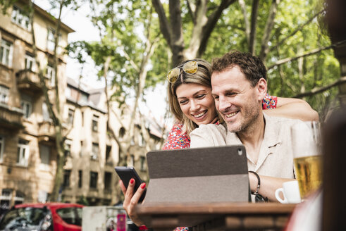 Smiling couple sharing tablet and cell phone at an outdoor cafe - UUF14313