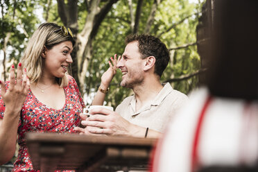 Happy couple talking at an outdoor cafe - UUF14316