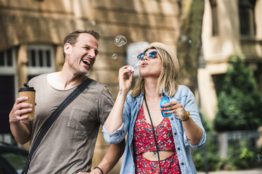 Happy couple with coffee to go blowing soap bubbles in the city - UUF14319