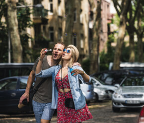 Couple blowing soap bubbles in the city together - UUF14322