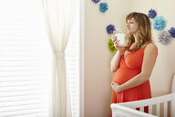 Pregnant woman drinking coffee and daydreaming in nursery - ISF14234