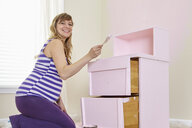Portrait of pregnant woman painting nursery dresser pink - ISF14240