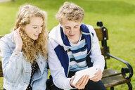 Teenage siblings looking at digital tablet on bench - CUF34141