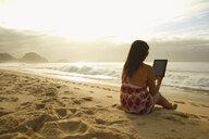 Mature woman using digital tablet on Copacabana beach, Rio De Janeiro, Brazil - CUF34150