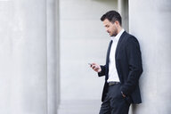 Young businessman leaning against wall reading texts on smartphone - CUF34159