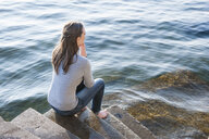 Young woman with eyes closed sitting on harbor steps - CUF34249