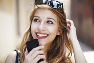 Sophisticated young woman with smartphone looking up - CUF34318