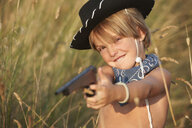 Portrait of boy in cowboy hat pointing toy gun - CUF34339