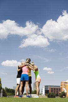 Exercise group huddled together in park - CUF34417