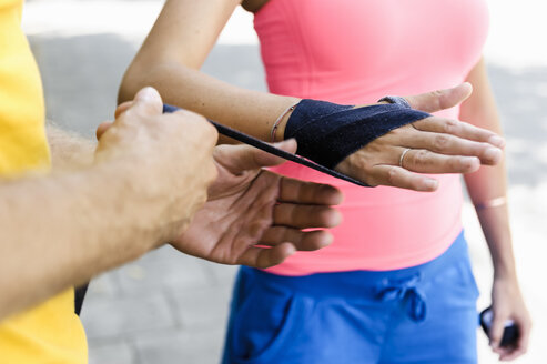 Personal trainer wrapping bandages around female boxers hand - CUF34420