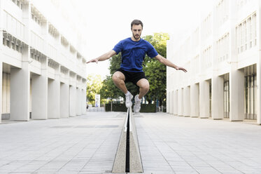 Young man jumping over divider - CUF34429