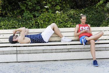 Two basketball players taking a break on park bench - CUF34435