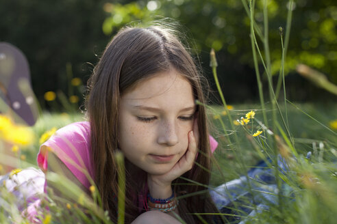 Girl lying in grass daydreaming - CUF34459