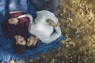 Romantic couple lying on blanket in forest - ISF14279