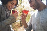 Couple smelling aroma of rose wine in forest - ISF14285