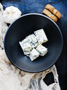 Garlic bulb and bowl of cubed blue cheese - ISF14309