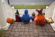 Children enjoying treats on steps - ISF14345