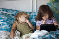 Girl and toddler sister reclining in bed using digital tablet - ISF14372