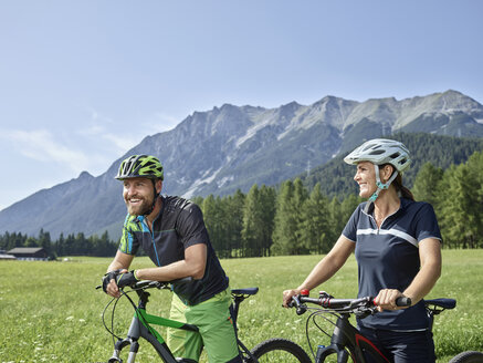 Austria, Tyrol, Mieming, happy couple with mountain bikes in alpine scenery - CVF00861