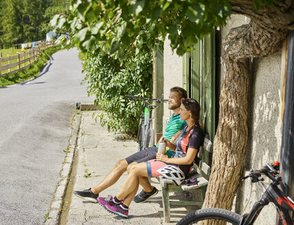 Couple with mountain bikes resting on a bench - CVF00864