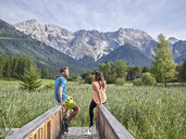 Austria, Tyrol, Mieming, couple resting on a boardwalk in the mountains - CVF00870