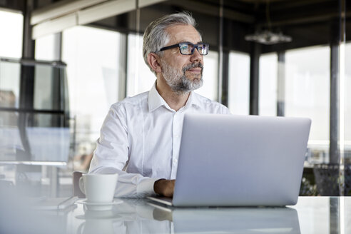 Businessman with laptop at desk in office thinking - RBF06316