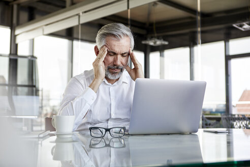 Businessman with headaches sitting at desk in office - RBF06319