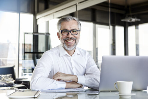 Portrait of smiling businessman with laptop at desk in office - RBF06325