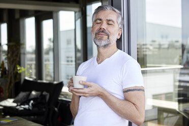 Man standing at French enjoying cup of coffee - RBF06328