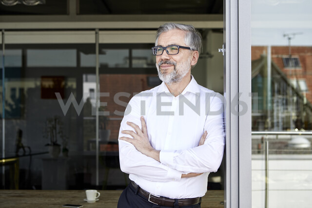 Smiling businessman standing at French door thinking - RBF06331