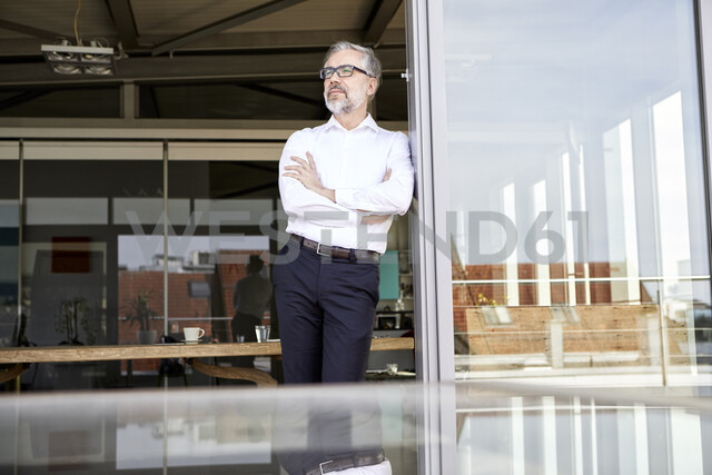 Businessman standing at French door thinking - RBF06334 - Rainer Berg/Westend61