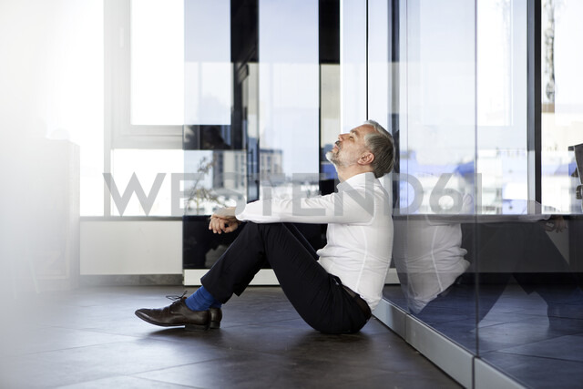Businessman sitting on the floor in office with closed eyes - RBF06349 - Rainer Berg/Westend61